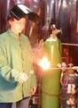An image-link to the Welding Program page, the image is of a Metal Fabrication student using a welding tank