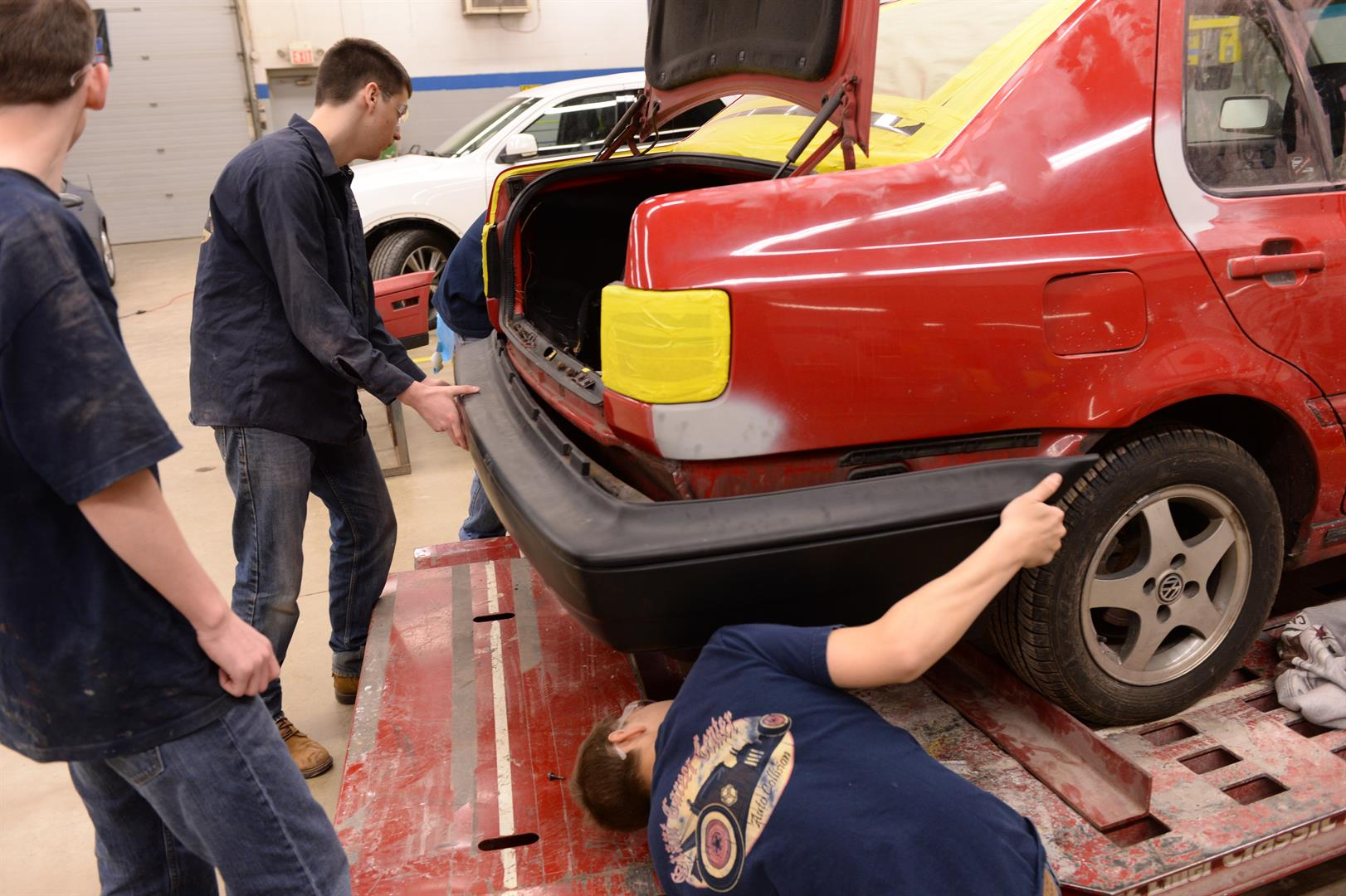 A group of students put a new bumper on a vehicle.