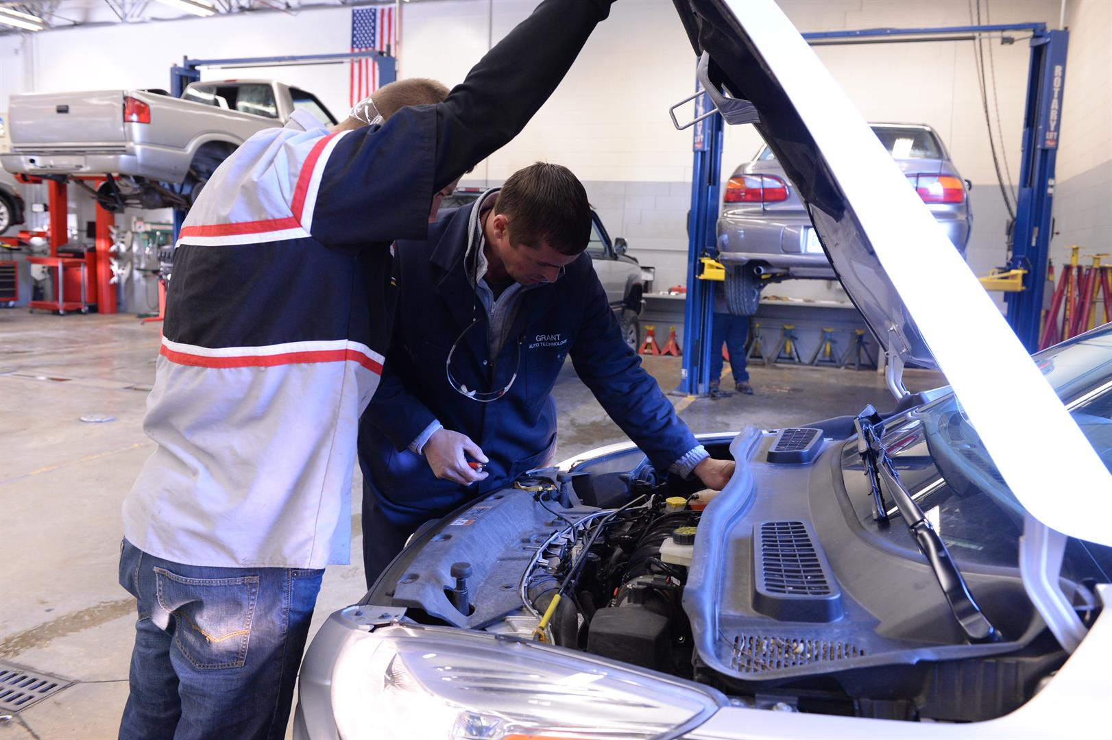 The Auto Technology instructor demonstrates to a student an engine task.
