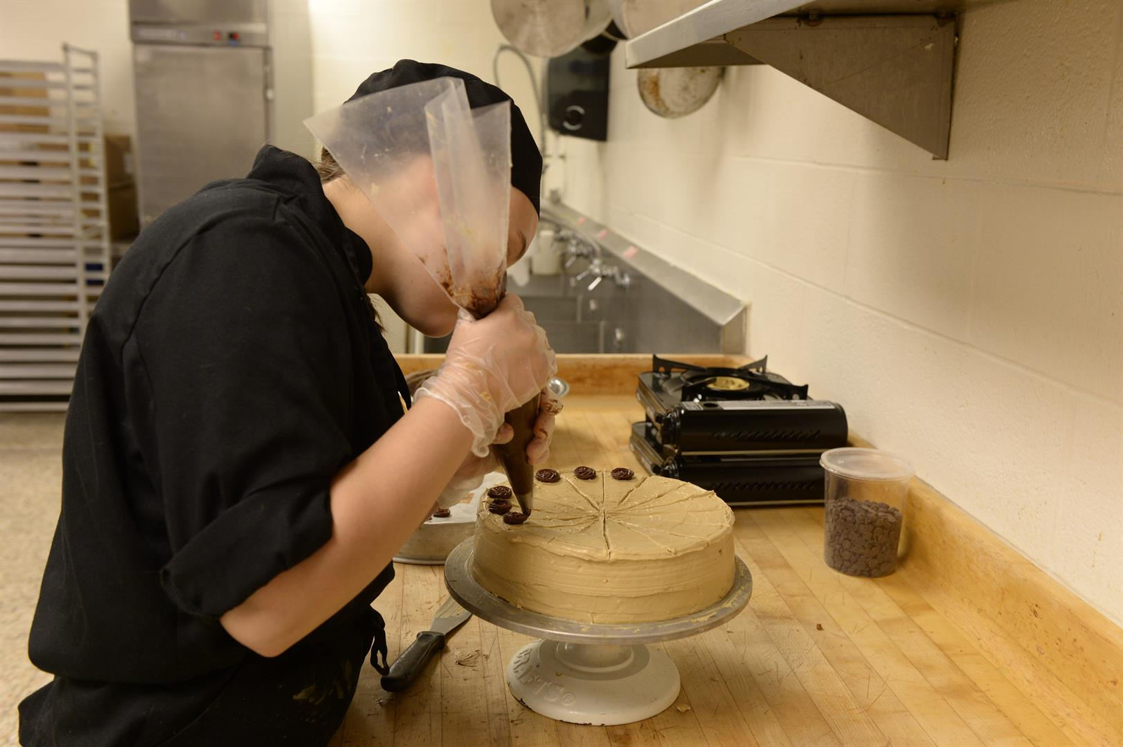A culinary art student pipes a cake.