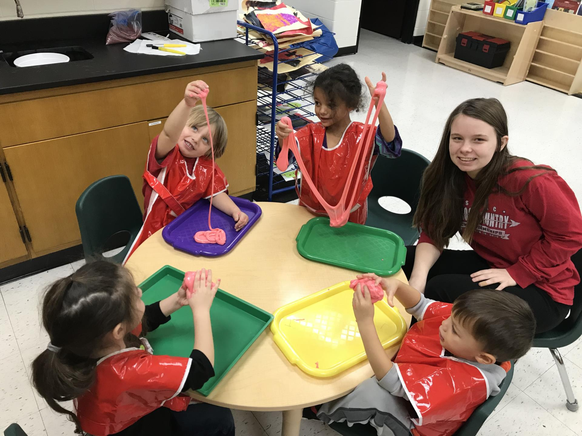 A picture of students and preschoolers playing with slime