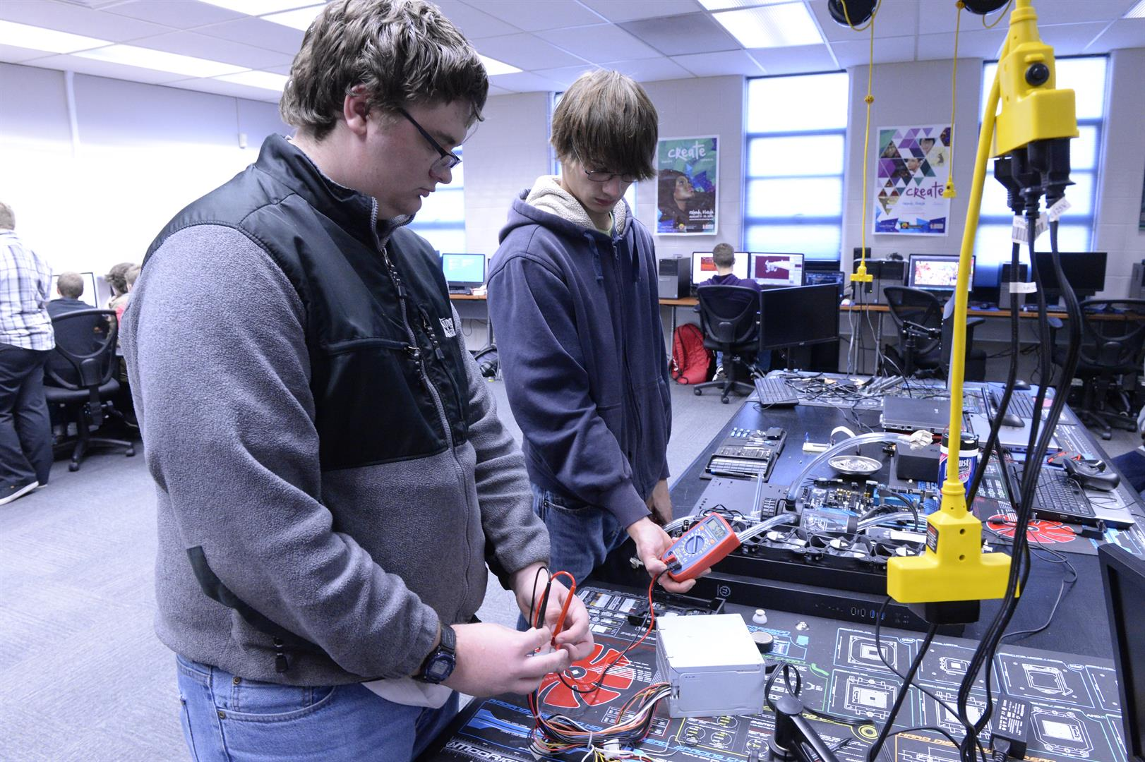 Two students work on a power supply.