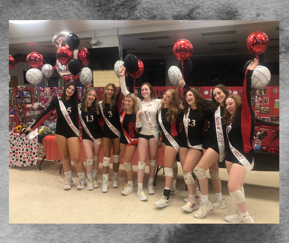 The Class of 2022 varsity volleyball athletes pose for a group photo on Senior Night held on Oct. 7. Student athletes are lined up with their arms around each other; smiling broadly and holding balloons in a very celebratory way.
