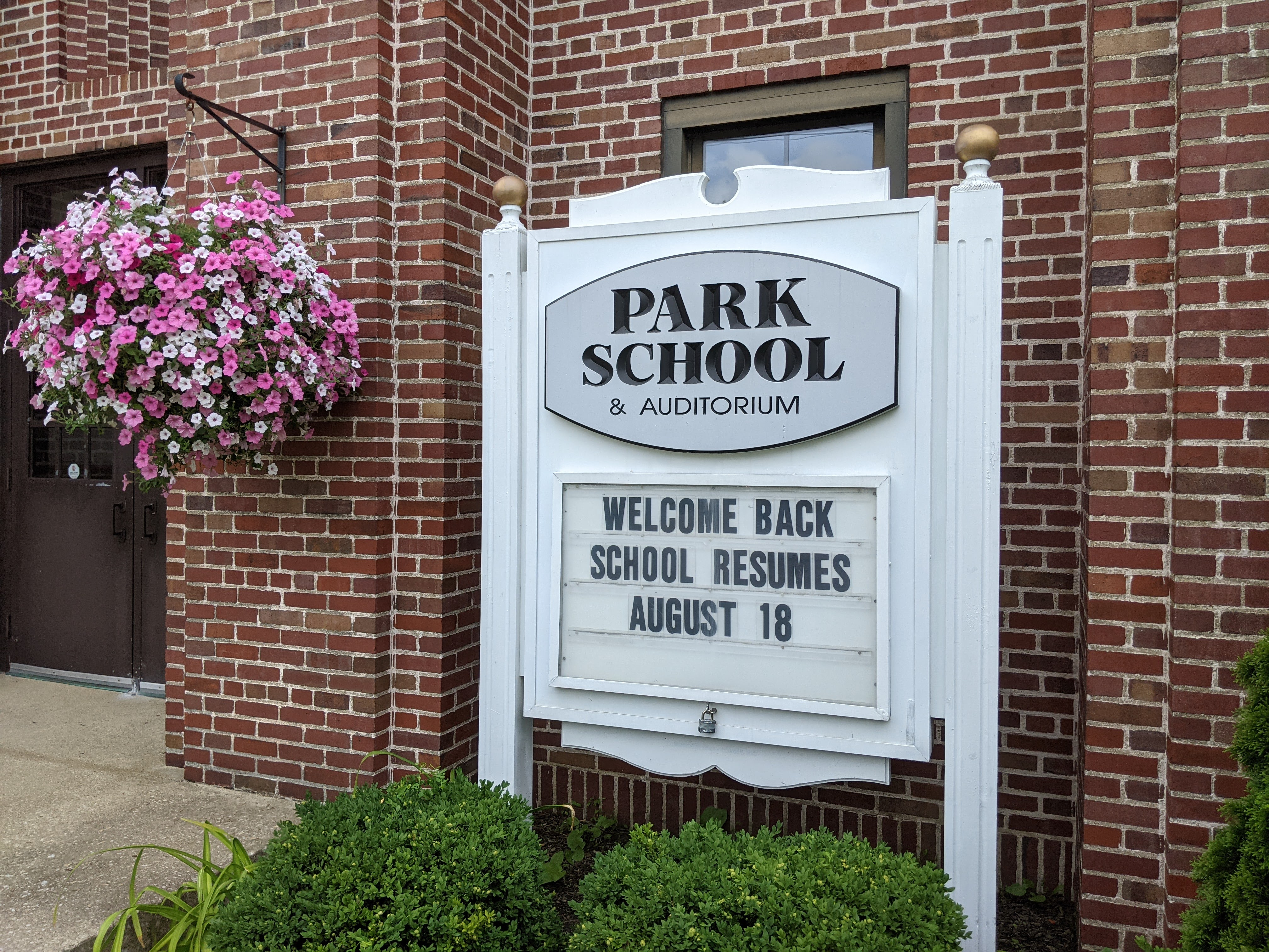 Marquee outside of Park Elementary:  Park School & Auditorium Welcome Back - School Resumes August 18; sign is in front of brick building with a large flower arrangement hanging beside it