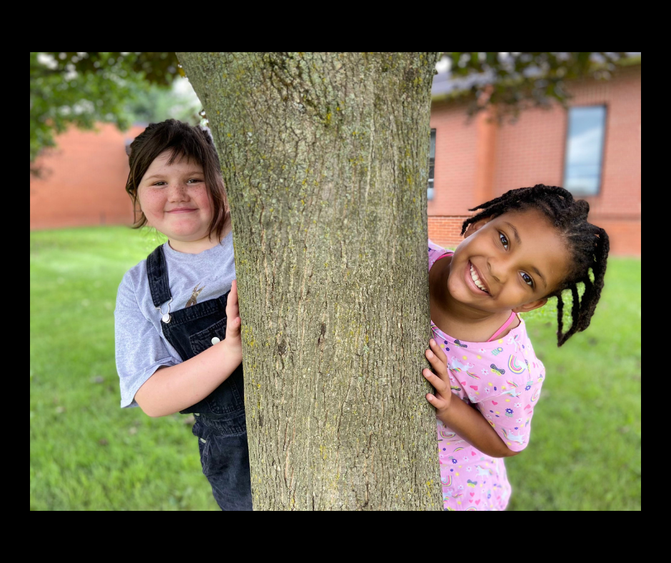 2021-22 School Year - 2 Munson Elementary students outside on the school grounds peeking out from opposite sides of a tree and smiling