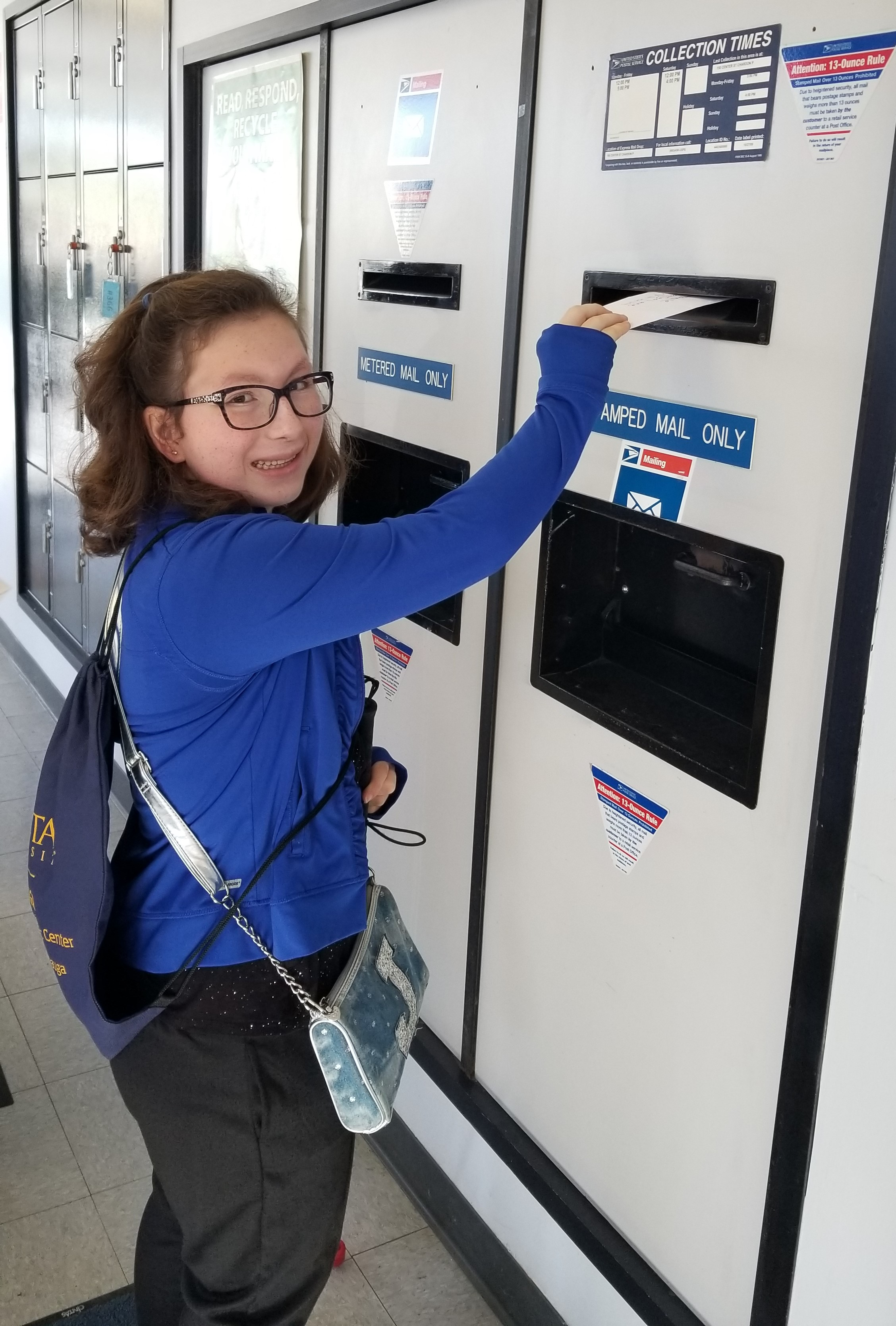 Chardon High School student putting a letter in a mail slot at the Chardon Post Office