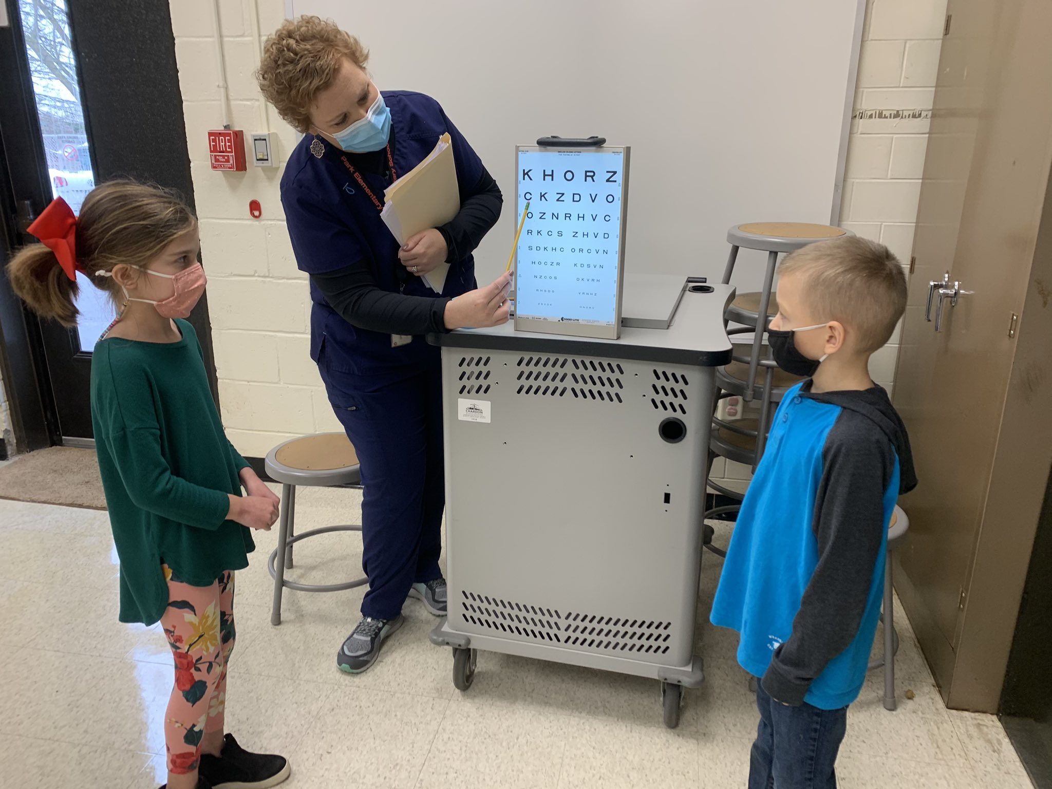 Nurse Chelsie Jackson at Park Elementary School in the 2020-21 school year involved in vision screening with two students.