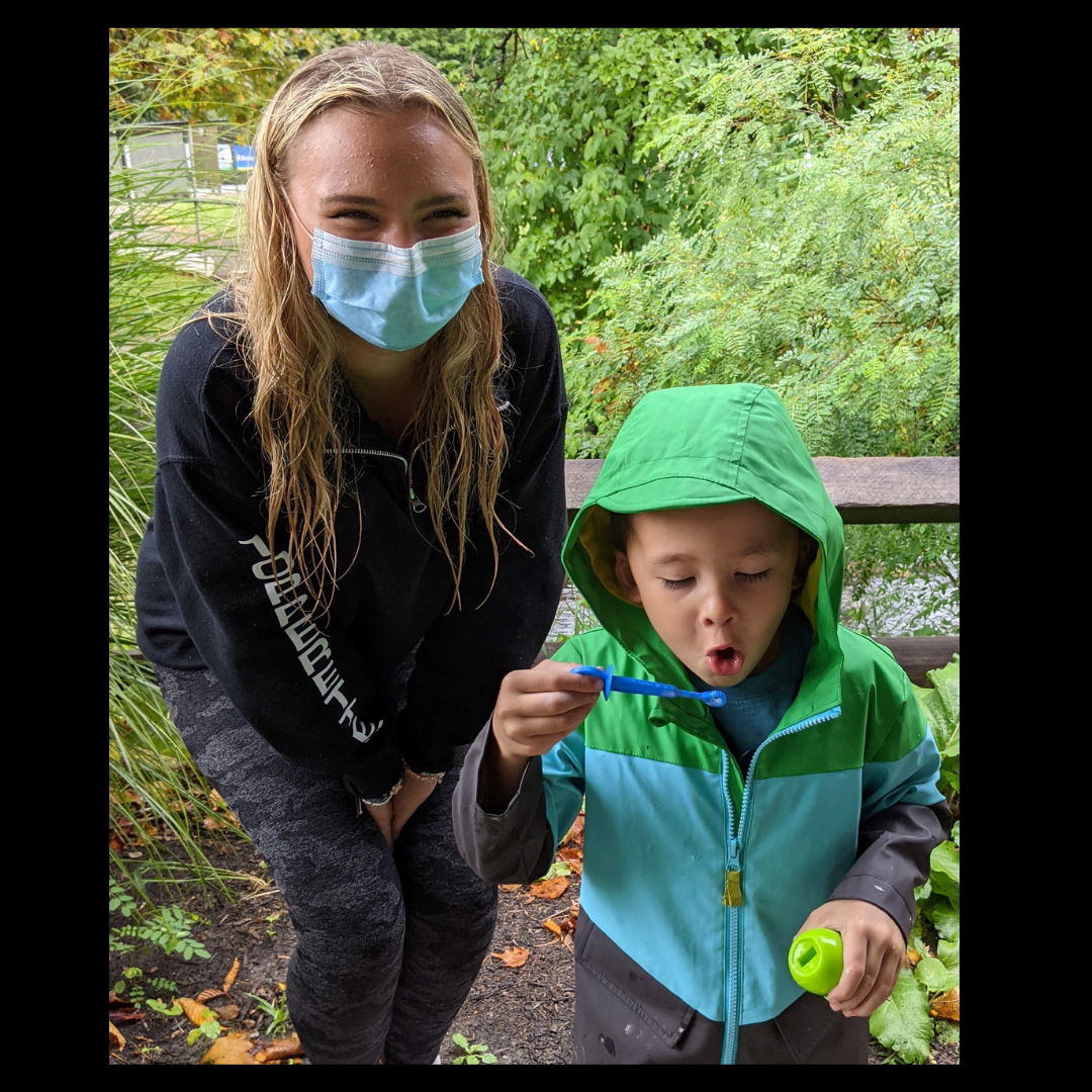 Chardon High School student (wearing a face mask) but eyes are smiling standing next to a Broadmoor School preschool student blowing bubbles at Eleanor B. Garfield Park in Mentor for the two schools' annual mentorship picnic