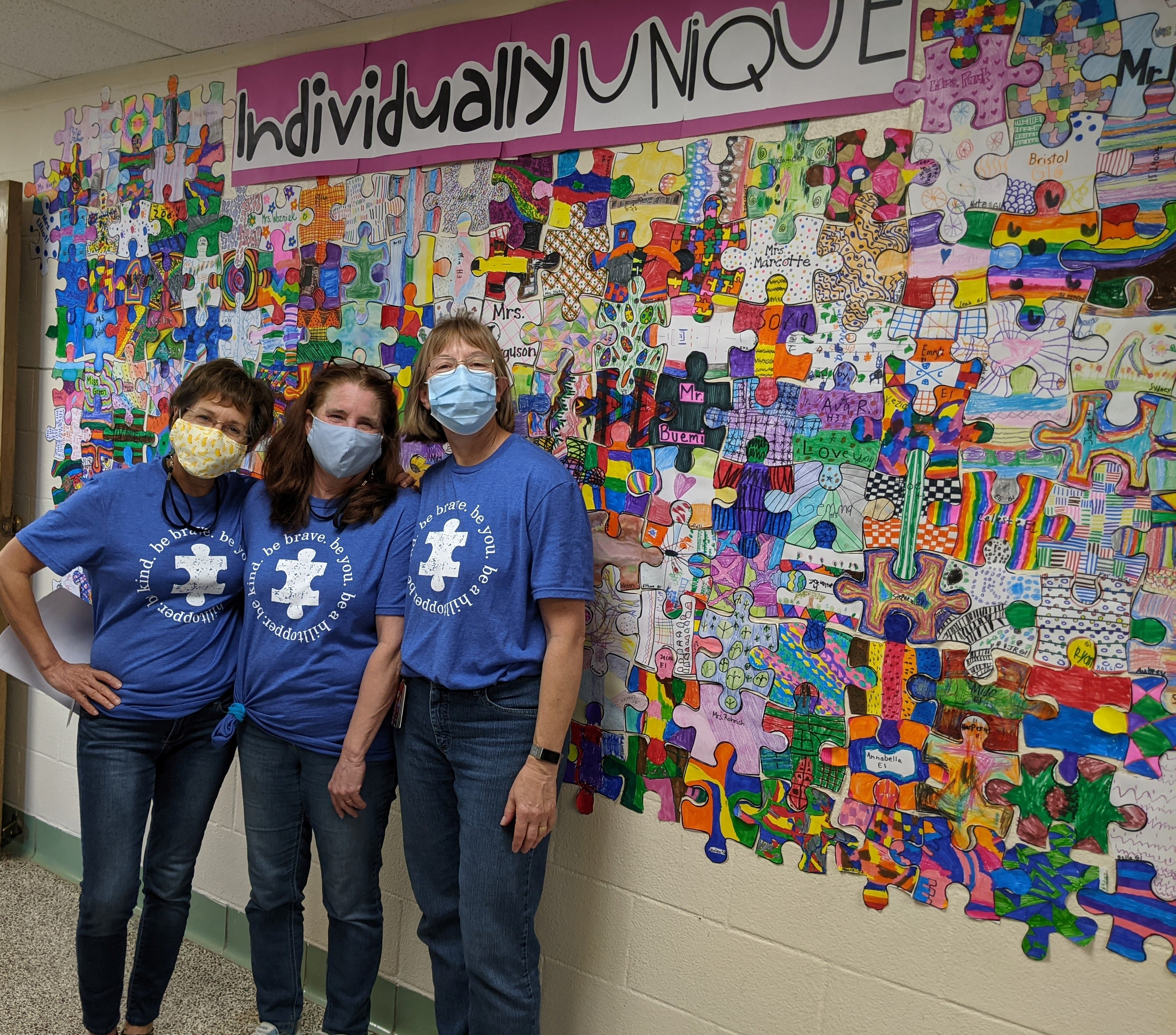 Rachel Diehl, Brenda Soulsby and Beth Stickley in Autism Awareness shirts in front of Munson Elementary's Individually Unique bulletin board on April 8, 2021