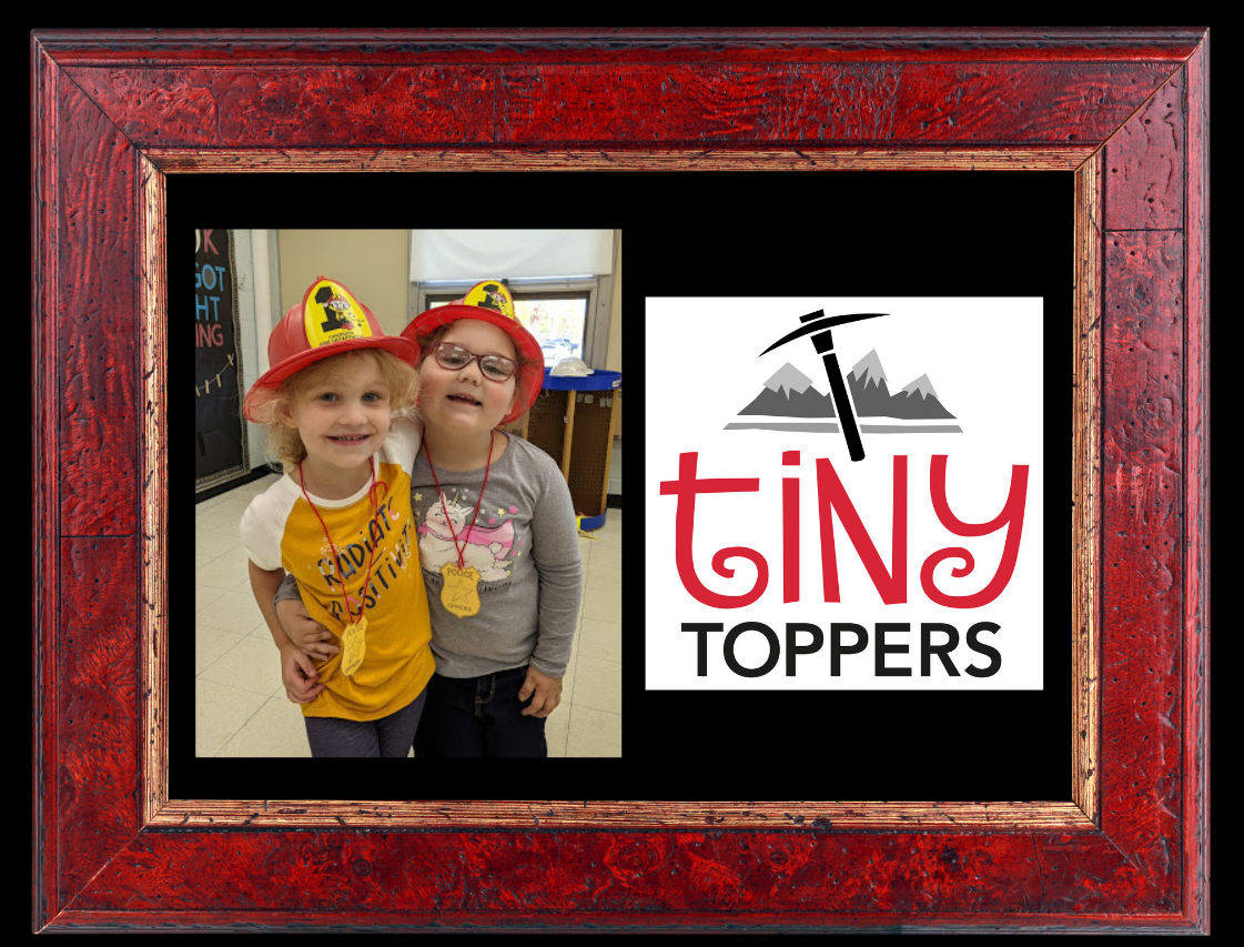 black background & red frame featuring centered photo of 2 Tiny Toppers preK students wearing plastic firefighter hats and hugging each other; and Tiny Toppers mountain axe logo - red/black/white