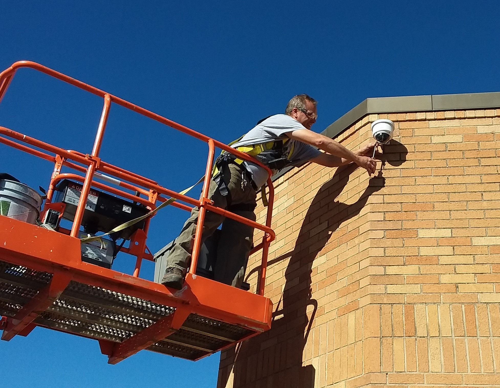 Lead Maintenance Staff Member Chris May on a lift making adjustments to an exterior light on the Chardon High School building