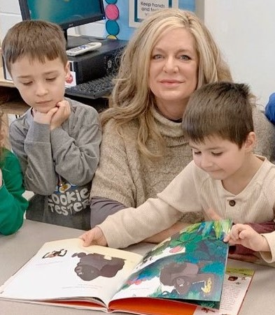 Director of Student Services, Linda Elegante, seated at a table with two Chardon Preschool students looking at a book with illustrations