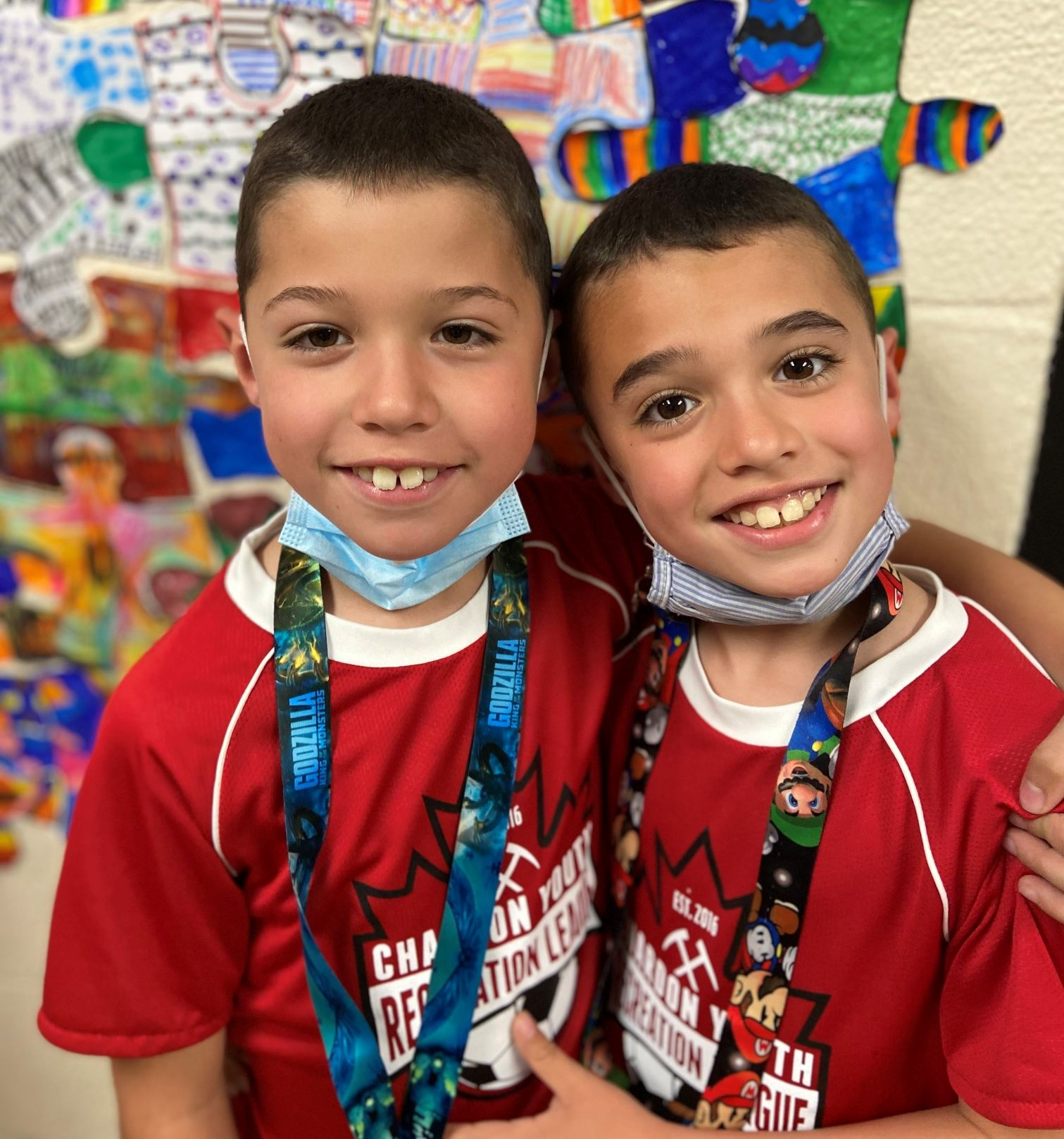 2 young male students at Munson Elementary standing in front of artwork on a wall smiling and with their arms around each other