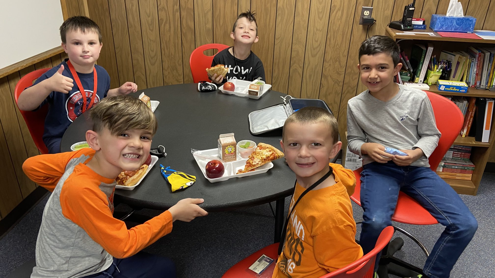 Group photo of 5 Munson Elementary students seated at a table - smiling for the camera - and having school lunches.