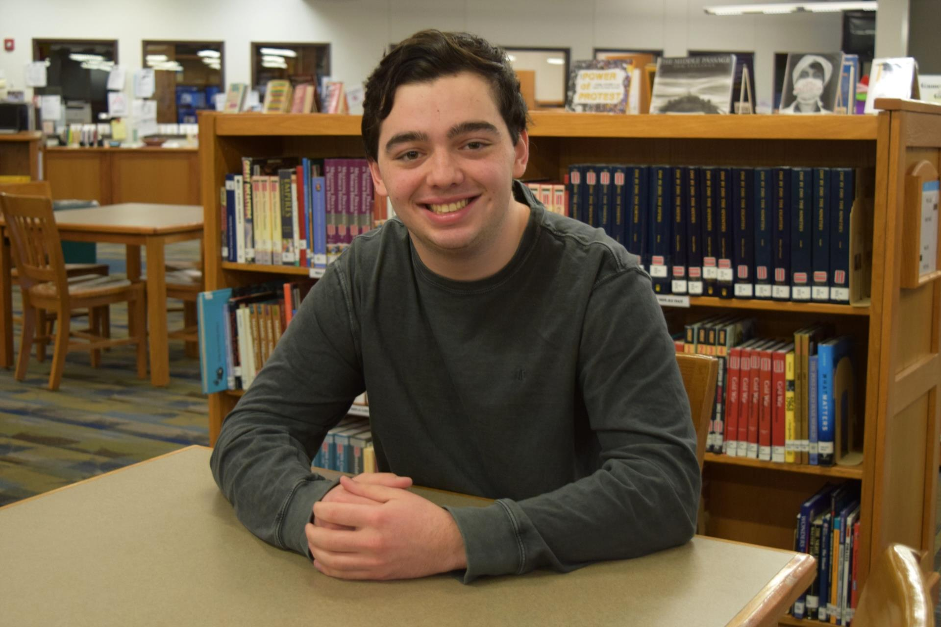 gabe ruano sitting at table in library