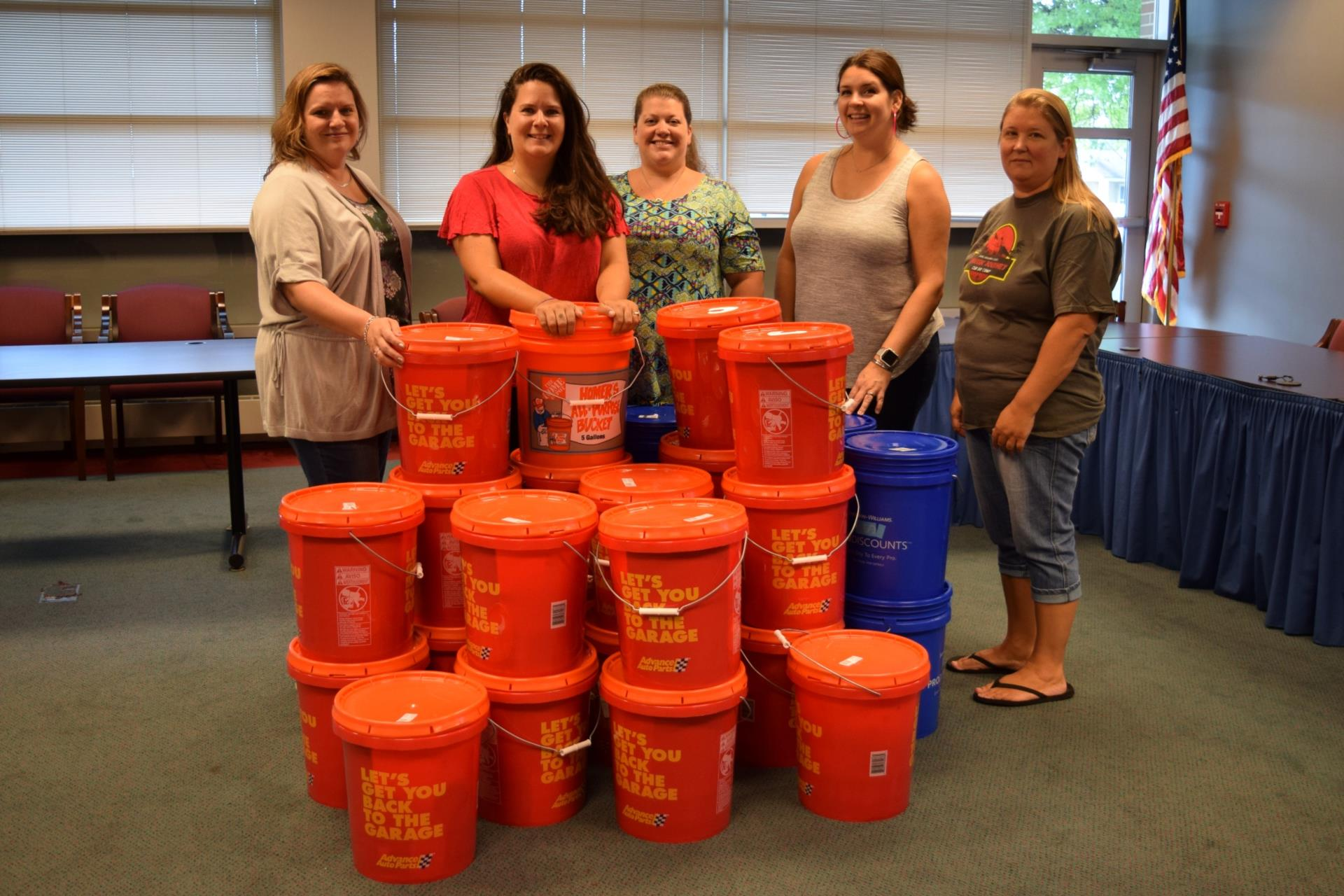 five women standingn with 29 five-gallon buckets