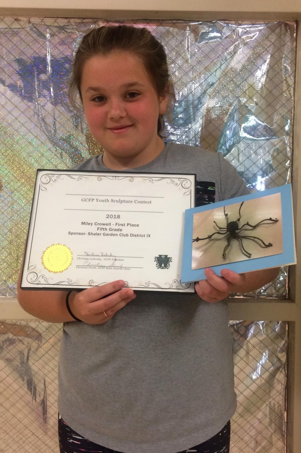 Miley Crowell holding certificate and photo