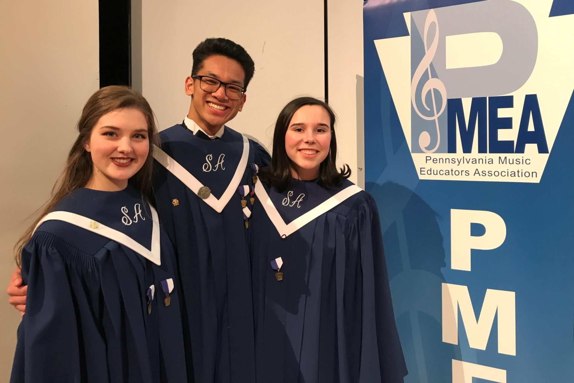 Kelsey Marshall, Alex Almonte, and Zoe Babbit in choir robes