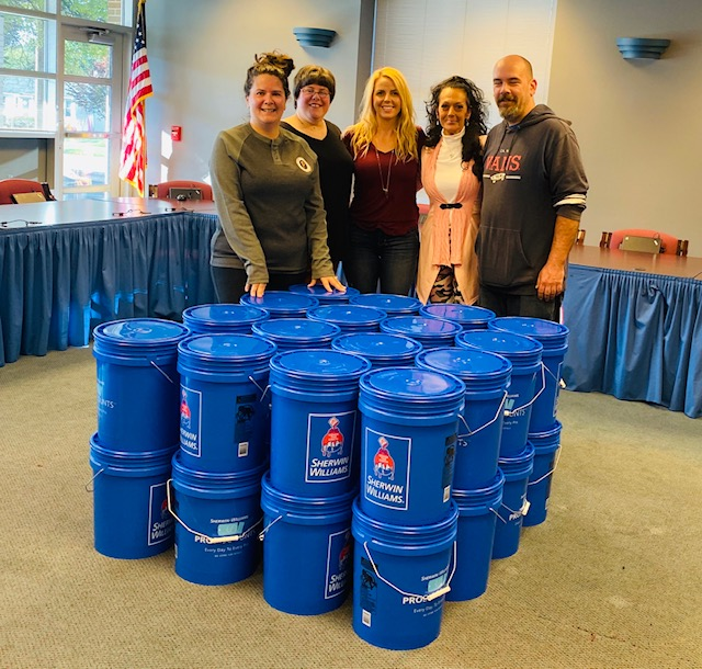 five adults standing behind stack of blue 5-gallon buckets