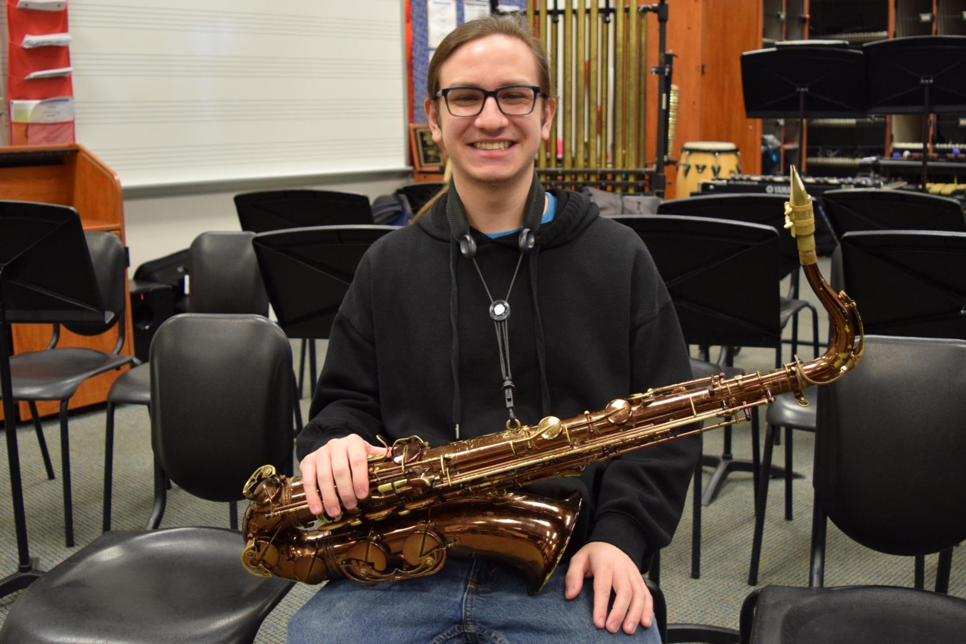 Zach Spondike sitting with saxophone on lap