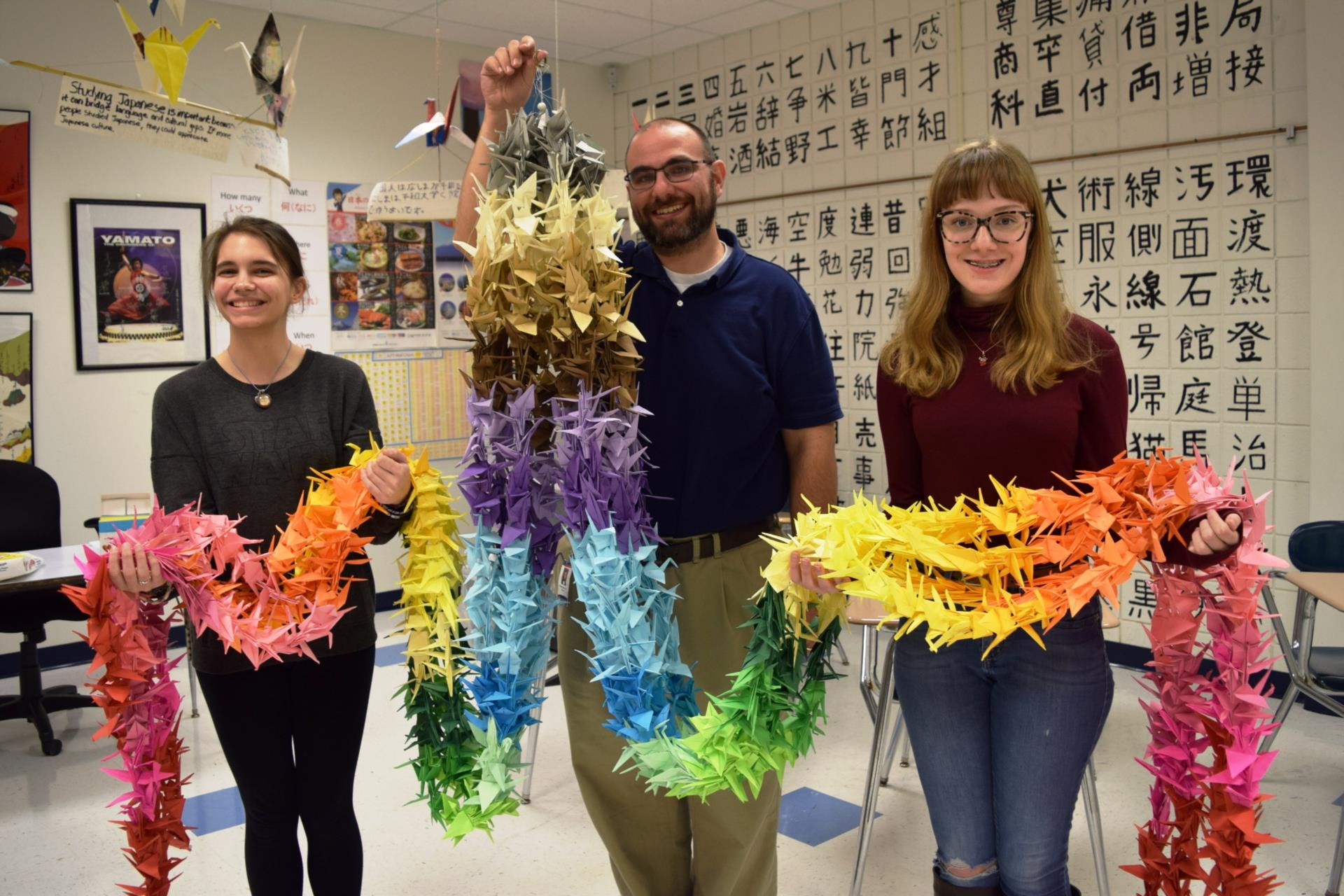 teacher and students holding paper cranes