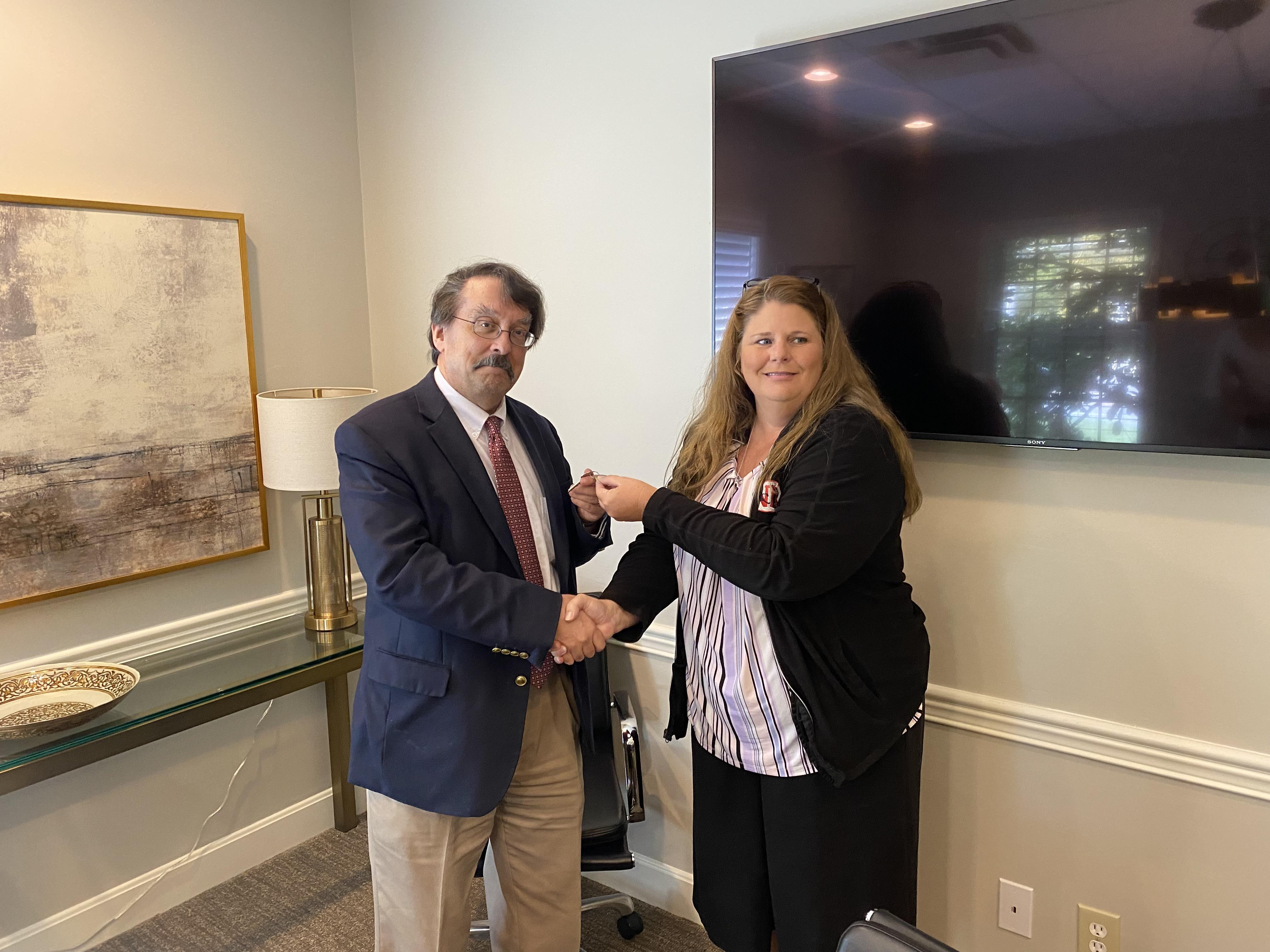 Board President Kristin Bennett hands keys to Kevin Clauson.