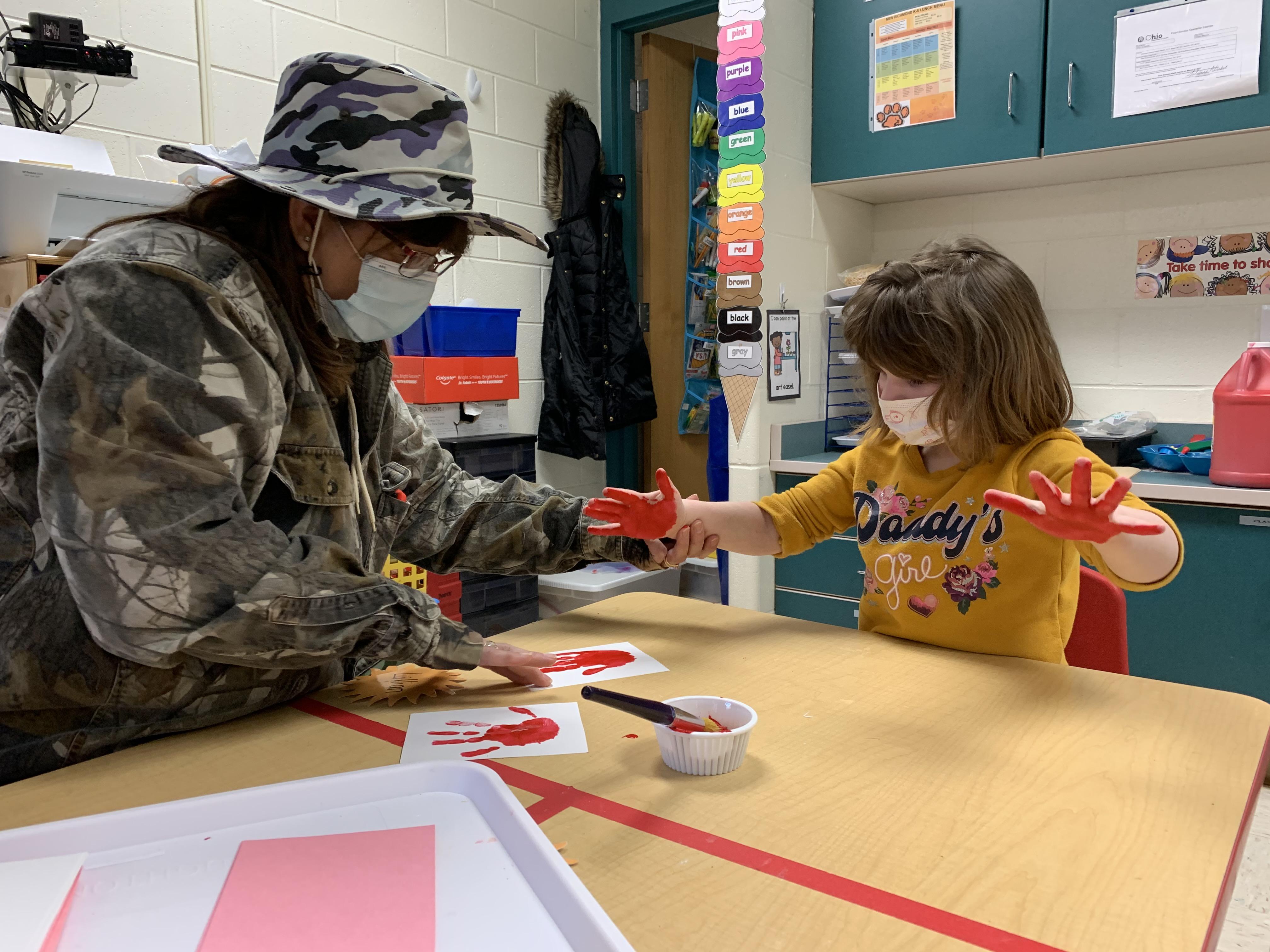 Teacher helps student make handprints with paint