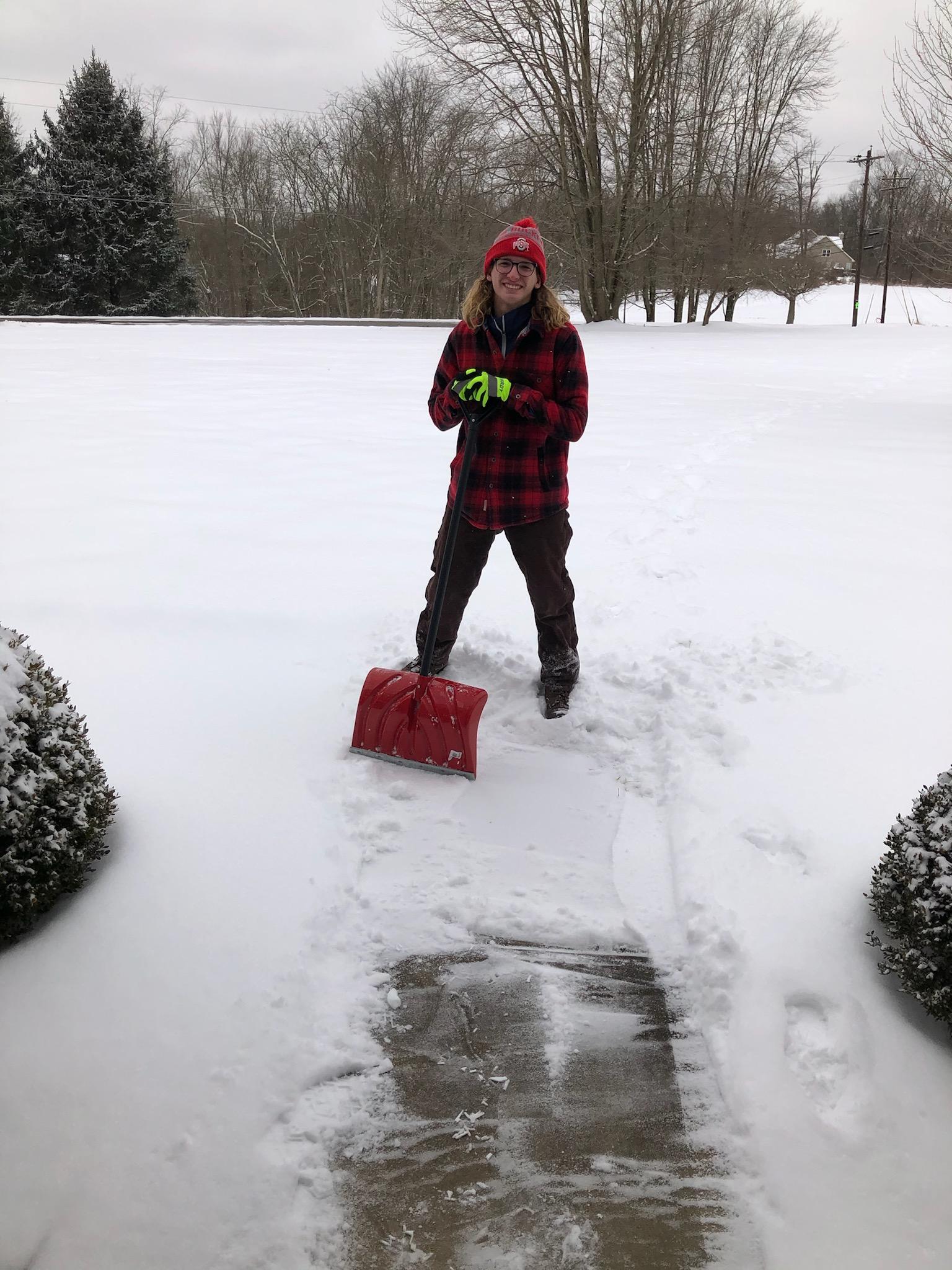 Student shovels snow from sidewalk