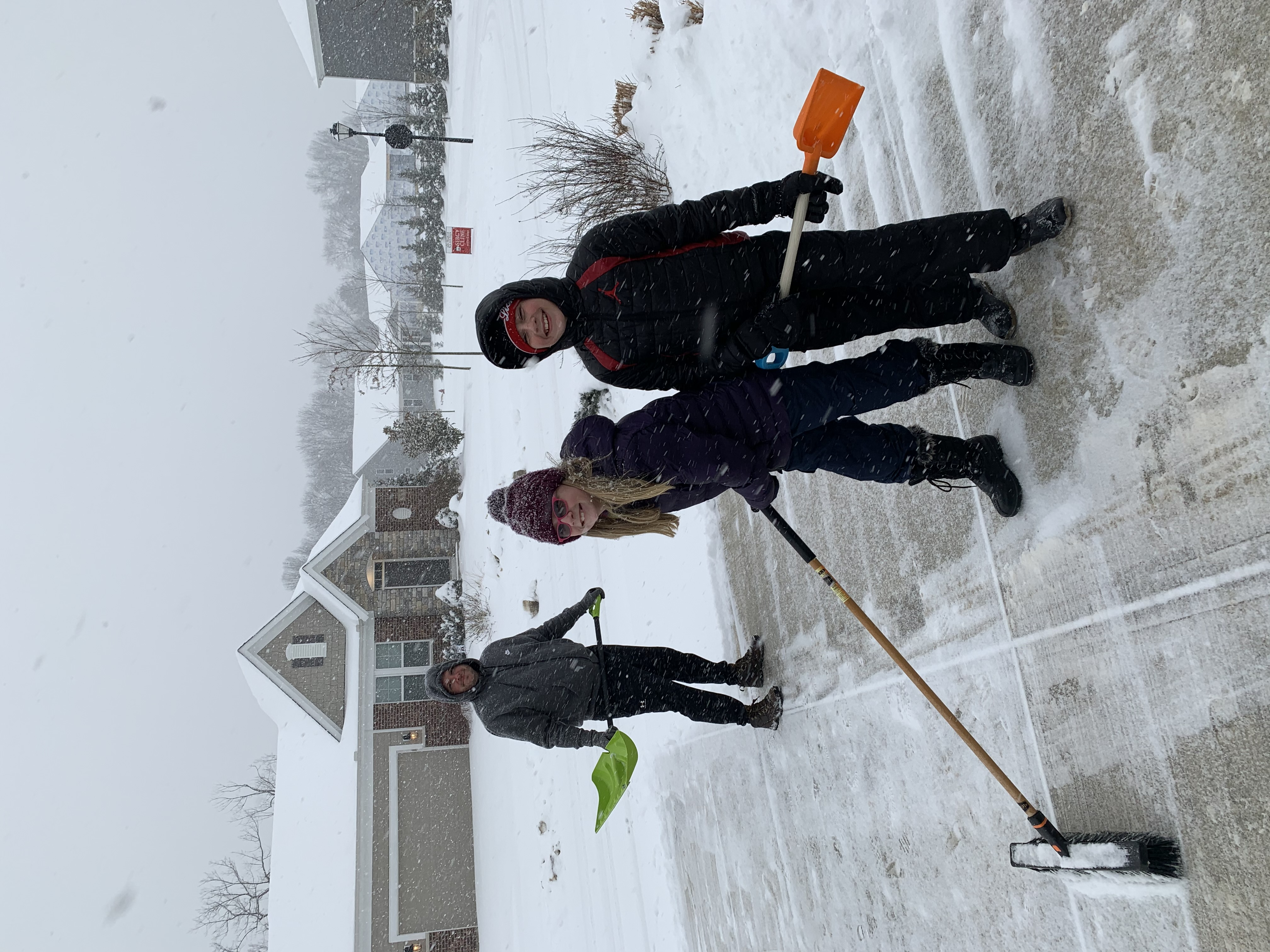 Students clearing snow from driveway